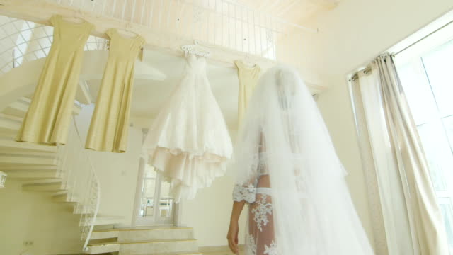 Bride in beautiful clothes suited to your wedding dress. Next hang the bridesmaids' dresses video