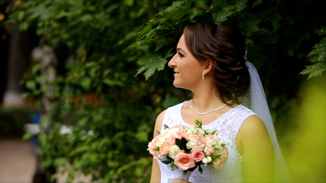 Bride in the wedding dress with bouquet in the park video