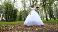 Bride in the wedding dress with bouquet walking in the park video