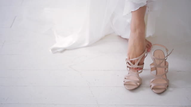 Bride in white dress wears beige shoes on wedding day on photo shoot video