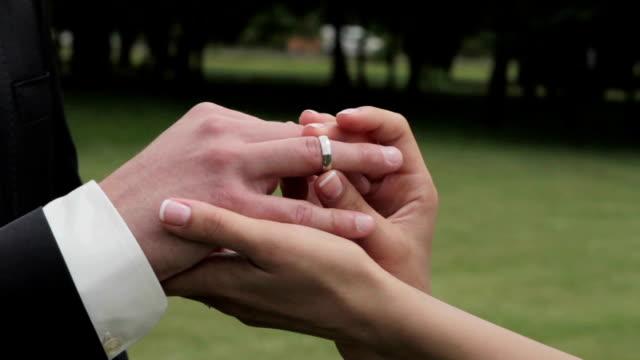 Bride putting wedding ring on groom's finger. video