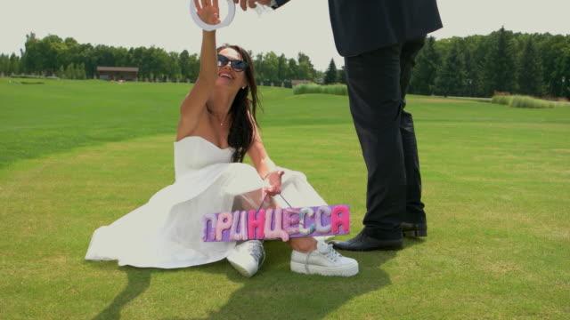 Bride sitting on green grass. video