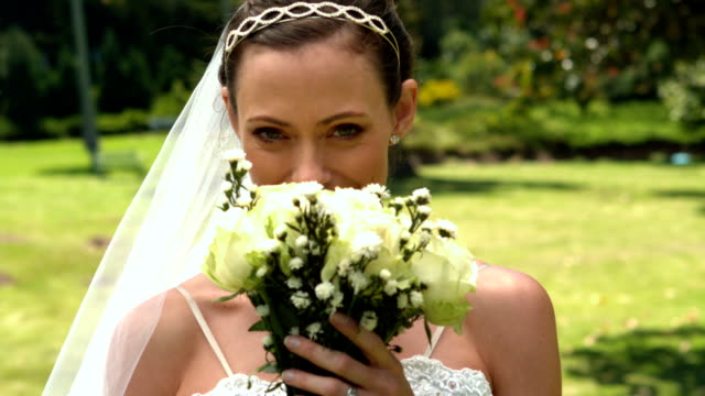 Bride smelling her bouquet in the park video