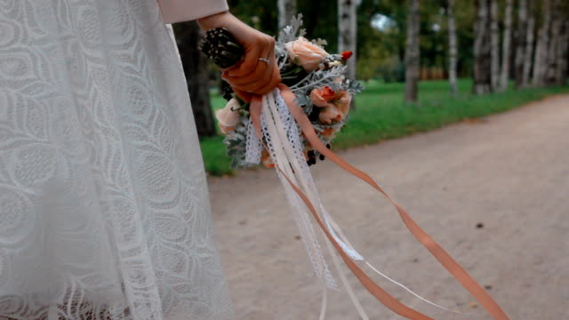 Bride with a beautiful bouquet of flowers walking in the park video
