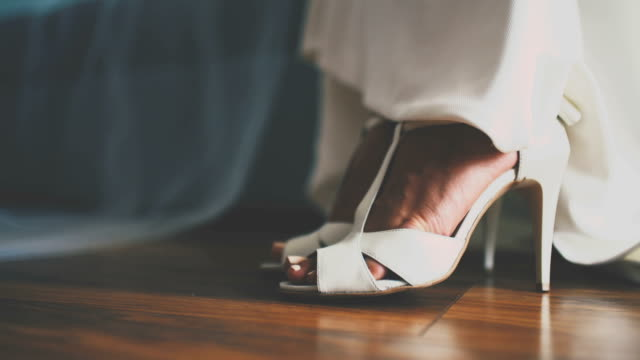 Bride's wedding shoes decorated with rhinestones on the wooden floor video