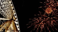 Bright Ferris Wheel in the night with great Fireworks background video