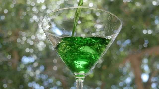 Bright Green Appletini Pours into a Martini Glass video