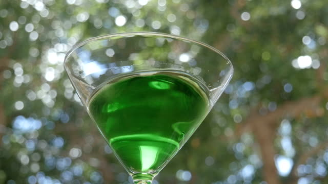 Bright Green Appletini Swirls in a Martini Glass video