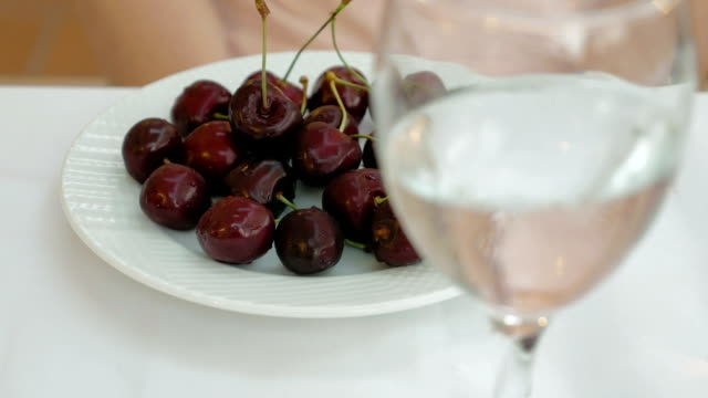 Bright red ripe sweet cherries on a white plate video