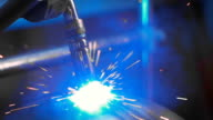 Bright sparks fly during the work of welding machine on production. Automated work of welding machine video