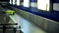 Bright yellow suitcase is traveling on conveyor belt in airport video