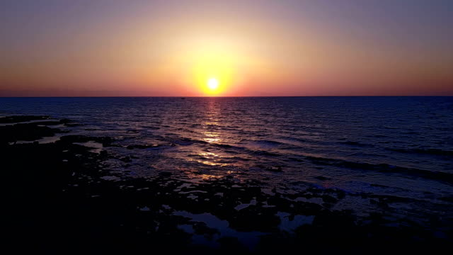 Brightly colored sunset over the calm Mediterranean Sea. Drone Point of View . Night video