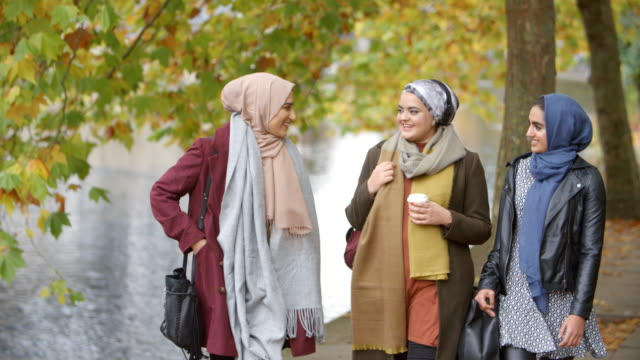 British Muslim Female Friends Walking By River In City video