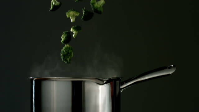 Broccoli is dropped into boiling water, slow motion video