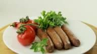 Broiled sausages and tomato rotate on a white plate video
