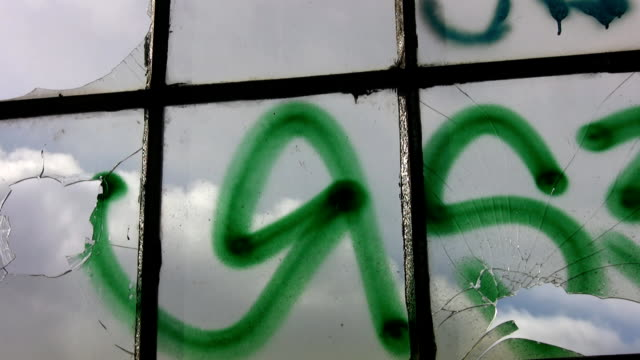 Broken window panes with graffiti. Timelapse clouds. video