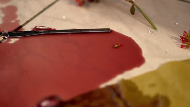 Broken wine glass falls into a puddle of wine video