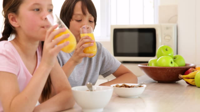 Brother and sister having cereal together video