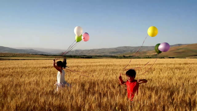 SLOW-MOT Brother and sister holding balloons and running video