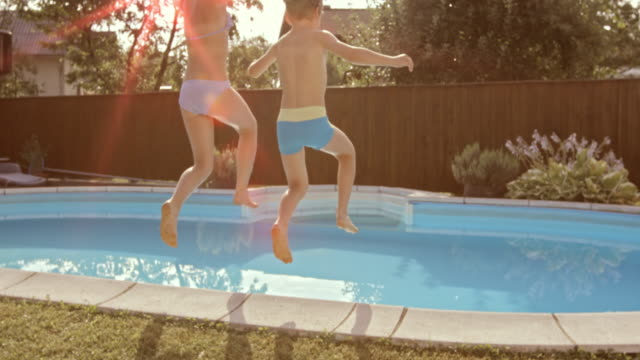 SLO MO DS Brother and sister jumping into the pool on a sunny day video