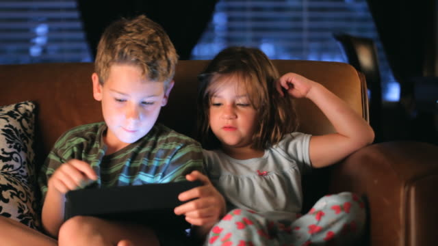 Brother and Sister Playing Handheld Video Game video