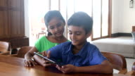 Brother and sister using digital tablet at home, smiling video