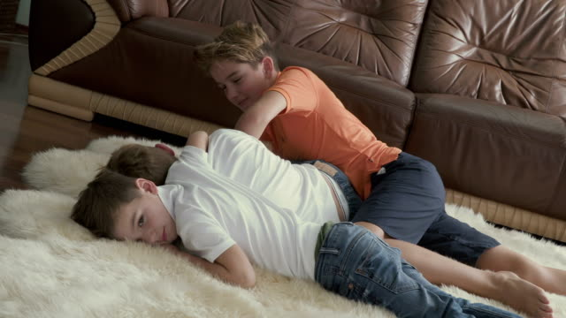 Brothers lays on carpet and fooling around at home video