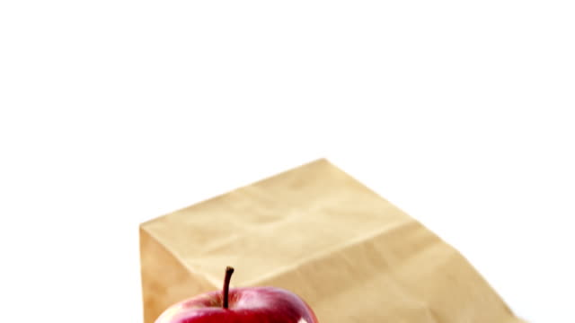 Brown paper bag and apple on white background video