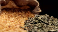 Brown sugar in gunny sack and a pile of dried green tea leaves video