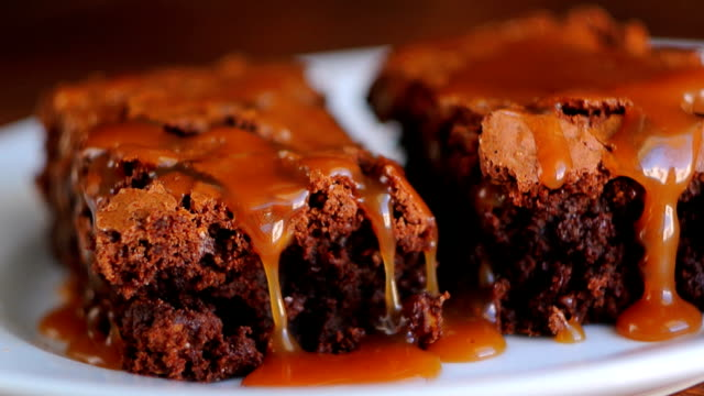 Brownie on a plate, on a wooden texture. Watered sweet salty car video