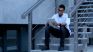 Browsing on Tablet PC while Young Black Man Sitting on Stairs video