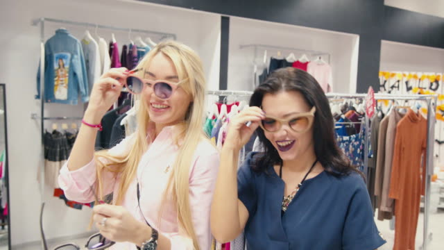 Brunette and blonde - two friends try on glasses and having fun video