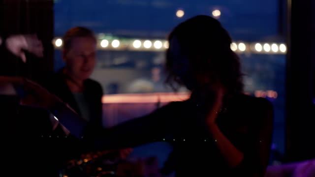 Brunette girl dancing on party in nightclub. Dj at turntable, man play saxophone video