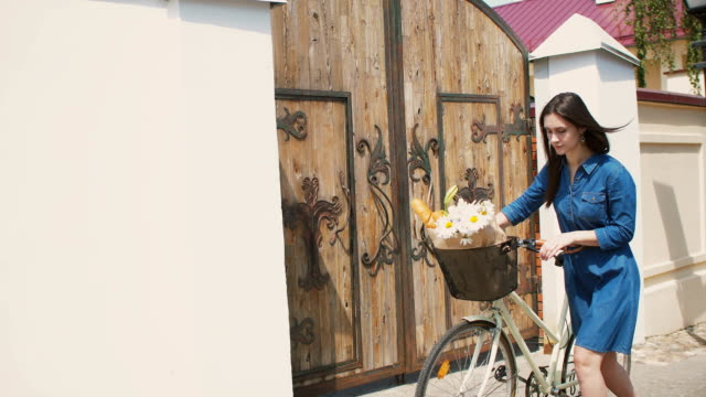 Brunette girl in a dress throws back her hair and walks her bike with flowers in a basket, FullHD, steadicam shot video