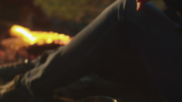 Brunette girl is taking a stainless mug of hot tea and drinks it while sitting next to a campfire in the evening. video