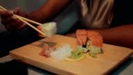 Brunette girl sitting at table in restaurant. Smile. Eat sushi by chopsticks video