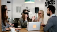 brunette girl tries app for VR helmet virtual reality glasses her friends and colleagues supporting her in modern office video