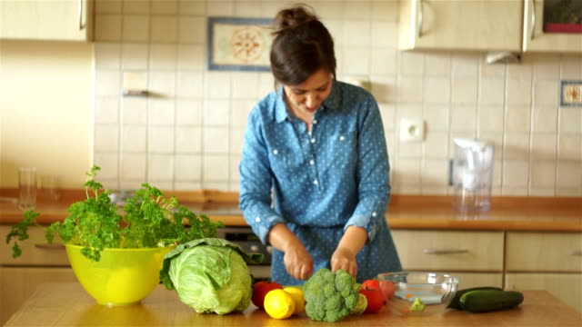 A brunette in a denim dress is dancing near the kitchen table. The girl is cutting the carrot. Healthy lifestyle. video