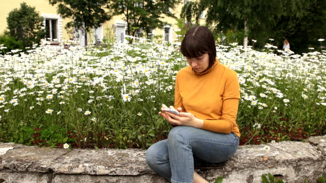 A brunette in a yellow turtleneck uses a phone sitting next to camomiles video