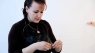 Brunette in black apron is busy with creating floral garland video