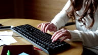 Brunette in white sweater working at a computer video