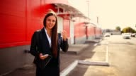 brunette outraged swears girl in street talking on phone smiling woman behind the outside red background video