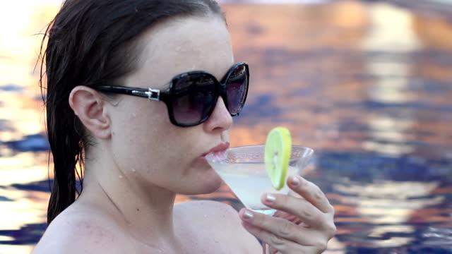 Brunette Sipping a Margarita Cocktail in a Pastel Colored Sunlit Tropical Pool video