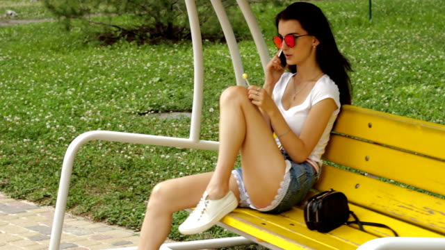 brunette sits on a swing on the phone and sucks lollipop video