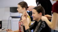 Brunette sits on chair and patiently waits until stylist creates her hairstyle video