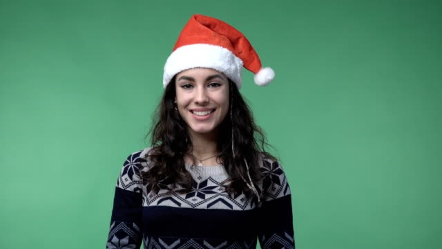 brunette woman in a red santa's cap smiling video