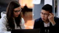 Brunette woman in glasses with a young asian male student with glasses sitting at table, discussing issue in front of laptop screen video