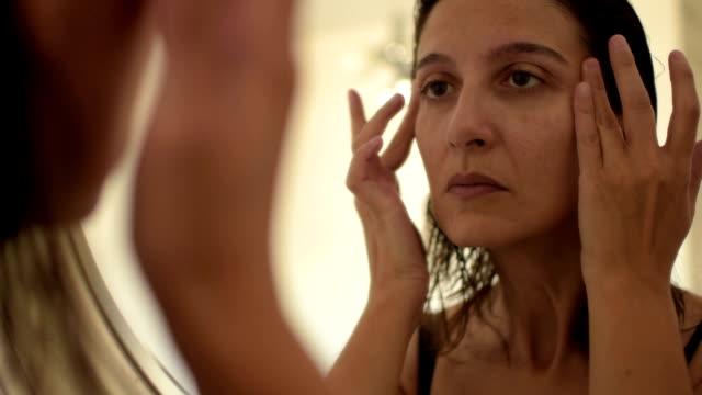 Brunette woman looking at skin in mirror video