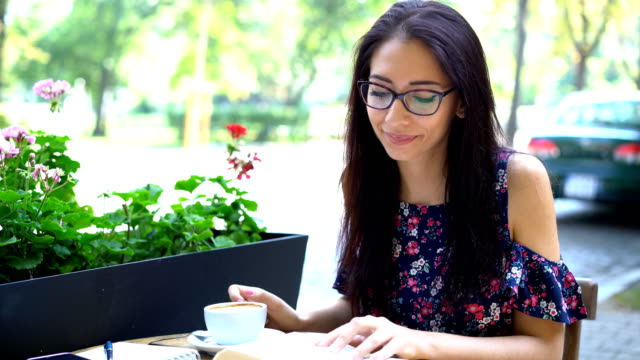 Brunette woman smiling at camera and drinking coffee video