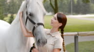 SLO MO Brunette woman stroking a white horse inside fence video